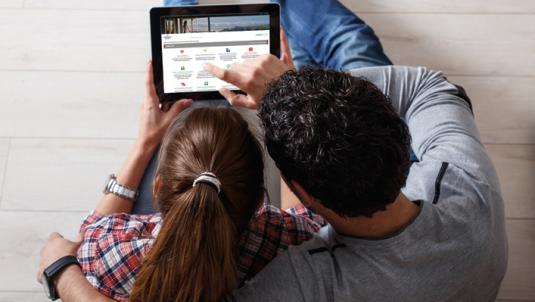 Man and woman looking at GNL website on tablet